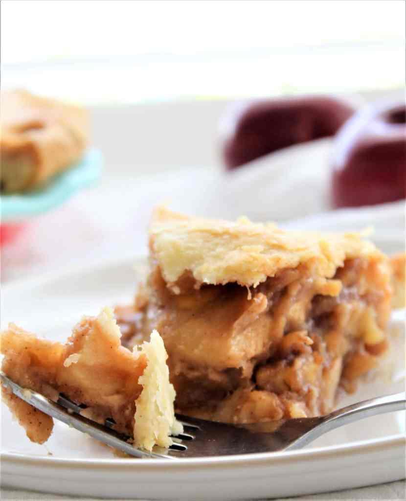 bite of apple pie on fork resting on white plate