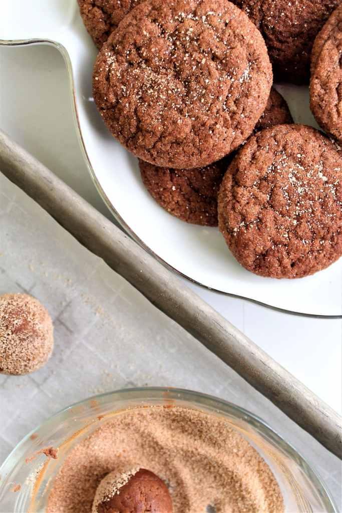 rolling cookies in cinnamon sugar