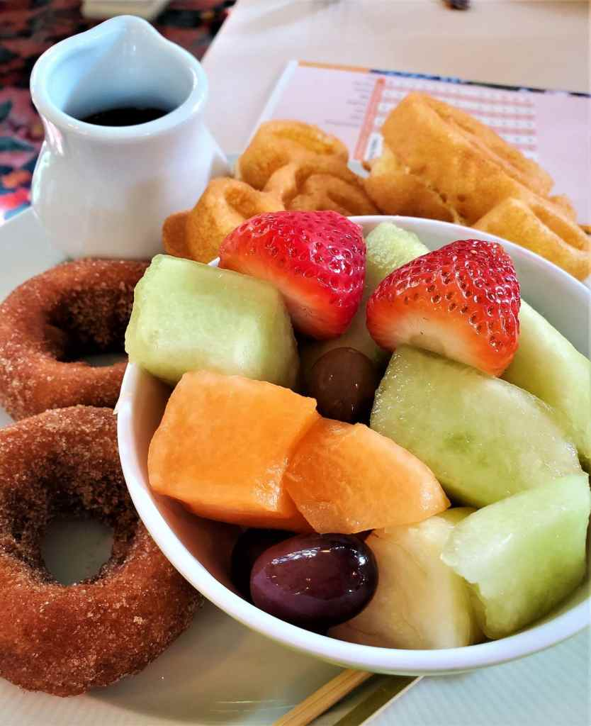 fruit in a bowl with donuts and Mickey waffles on the side
