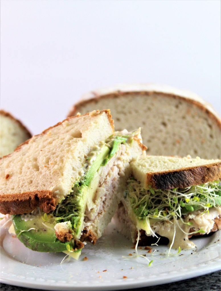 sandwich made on sourdough with turkey, cheese, and avocado