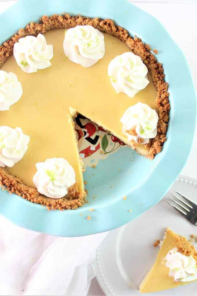 overhead shot of one piece of key lime pie on a plate next to whole pie