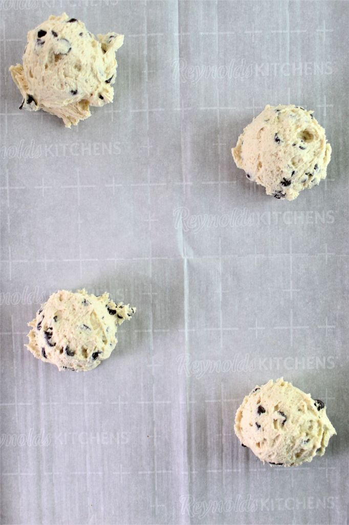 four scoops of cookie dough on a baking sheet