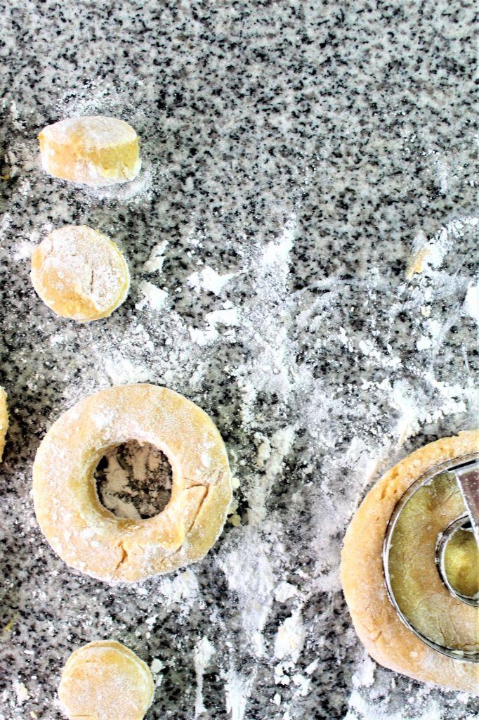 cutting out pumpkin donuts