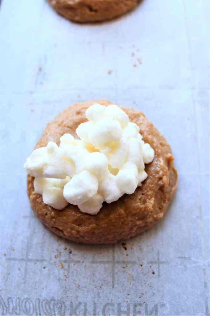 adding marshmallows to cookies to bake