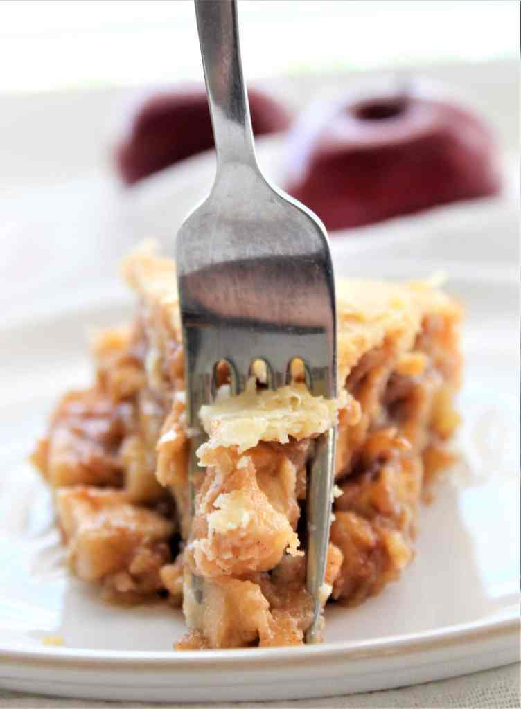 fork cutting through slice of apple pie on white plate