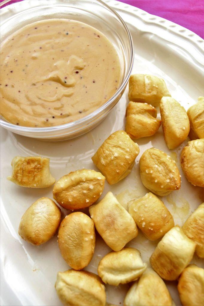 pretzel bites on white platter with cheese sauce