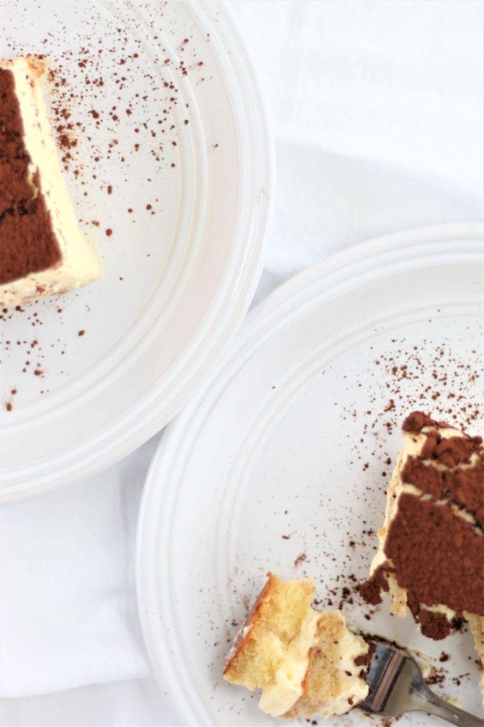 overhead shot of two pieces of tiramisu on white plates