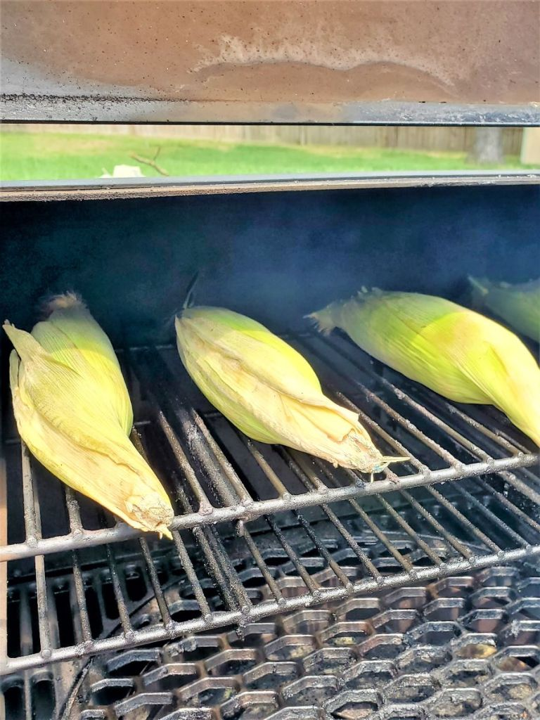 three ears of corn on top shelf of grill