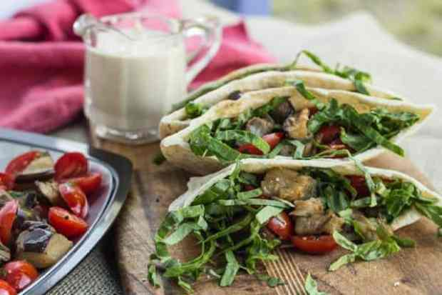 side view of Roasted Eggplant and Tomato Pitas with pitcher of Lemon Tahini Sauce in back