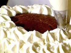 Piping whipped cream on chocolate snowball cake