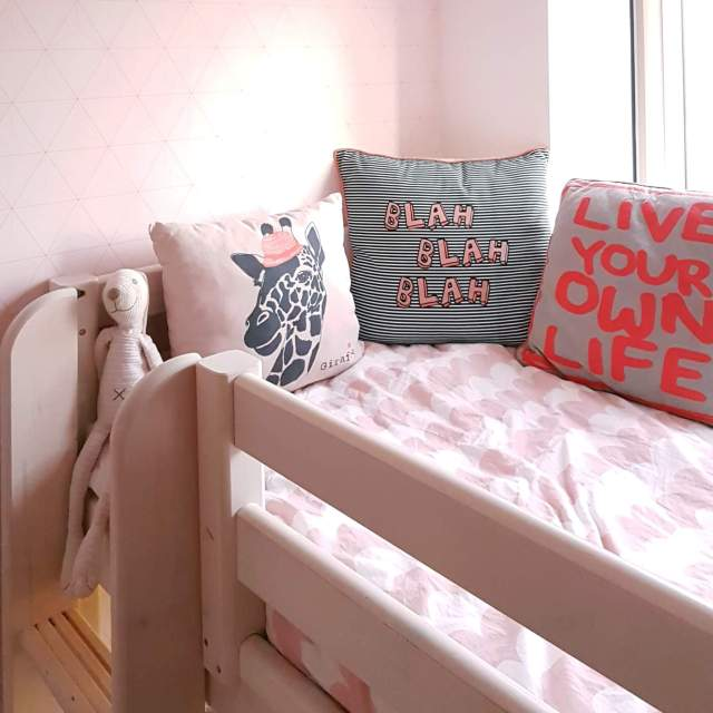 Binnenkijker: kleine witte kinderkamer met roze en geel