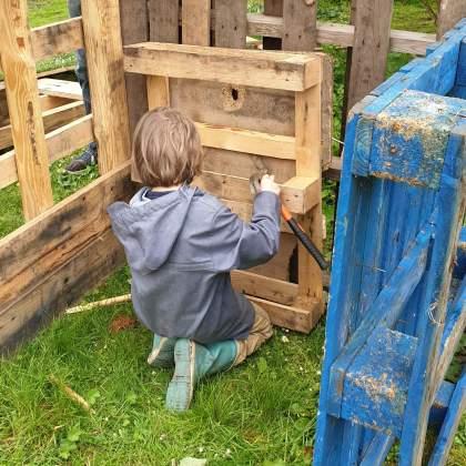 Buitenspelen in je eigen tuin: met deze tips kun je kinderen stimuleren - leren klussen met oud hout