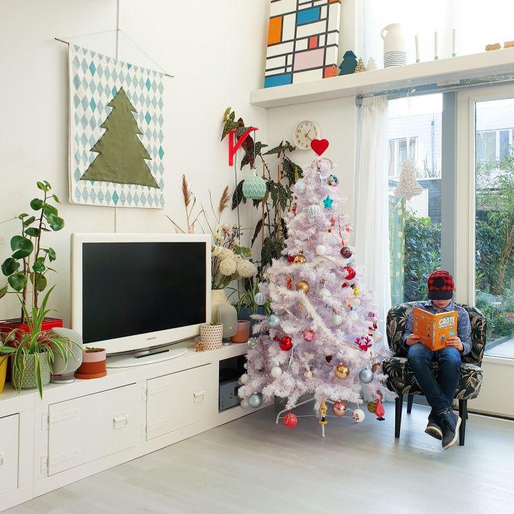Binnenkijker: kleurrijke woonkamer met witte basis plus groen en vintage. Fijne plek in relaxstoel en uitzicht op de tuin.