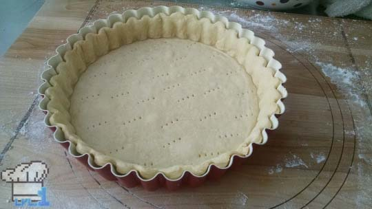 Tart dough has been rolled out and pressed into the pan for the tart shell before baking.