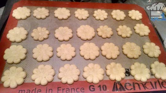 Baked flower cookies on pan, ready to be decorated.