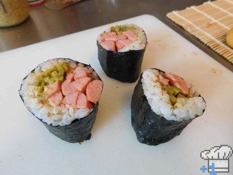 Sliced hot dog sushi rolls resting on mat, awaiting the buns.