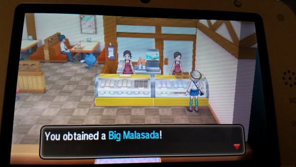 Screenshot from the Pokemon game series of a big malasada being purchased at the bakery.
