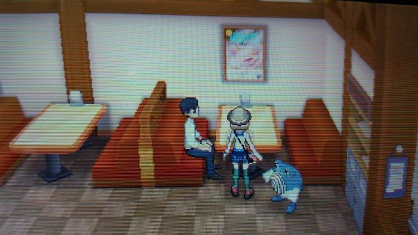 A screenshot from the Pokemon game series of a big malasada poster in the bakery.