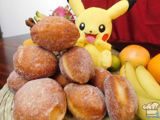 A hungry Pikachu is looking at the mound of sugared malasada doughnuts from the Pokemon game series.