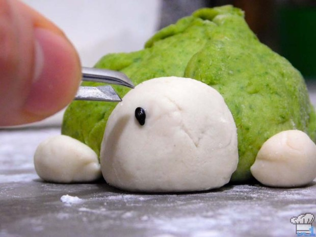 Applying the black sesame seed eyes to the Paper Mario Koopa Bun with tweezers, before steaming.