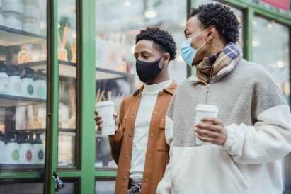 trendy black men walking on city street with takeaway coffee in hands