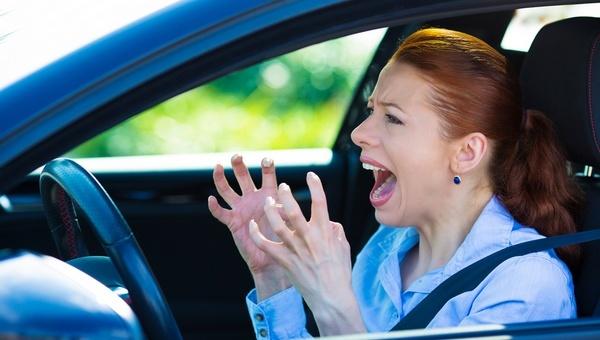 Foto van vrouw die gefrustreerd achter het stuur van haar auto zit