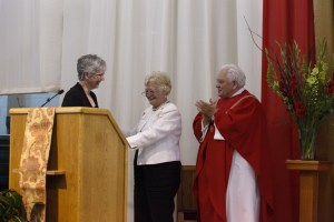 Mrs. Joan Troy accepts congratulations from Mrs. Anne Stahel and Msgr. Gerald L. Lewis, at a ceremony held at Cardinal Gibbons High School