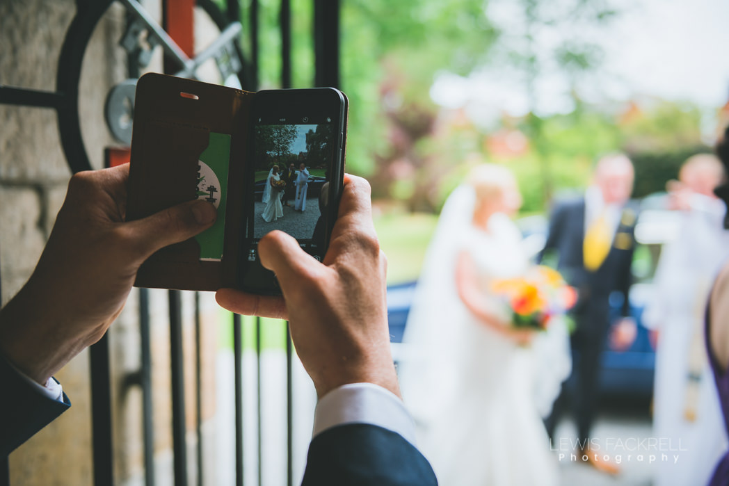 guest taking photo on phone at wedding