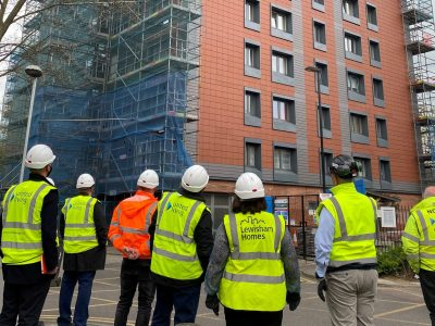 People in hard hats and yellow safety vests look up at a part-scaffolded tower block