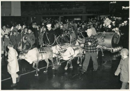 Reindeer pulling Santa's sleigh in a Christmas Parade at Boistfort and Market Street. In the background is the sign for Schwartz Men's Wear, Florsheim Shoes, Marr's Drugs and Burnett's Jewelry Store on the corner. The high window is in Coffman Dobson's First National Bank of Washington. Photo courtesy: Lewis County Historical Museum.