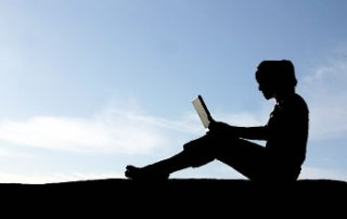 Silhouette of laptop user with sky in background