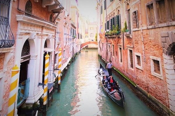 Photo de Venise: la gondole sur le canal, les murs en briques travaillés par l'humidité, des couleurs superbes