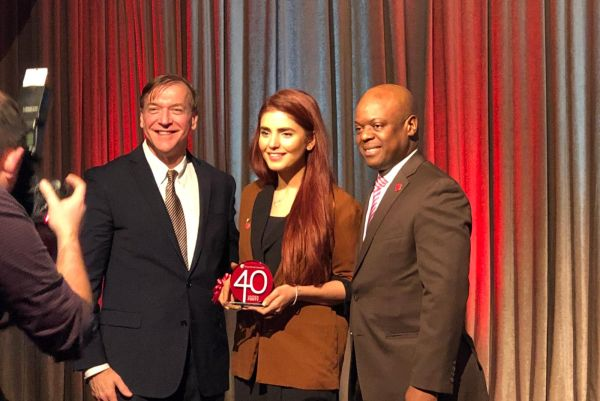 Momina Mustehsan with Stony Brook President Samuel L. Stanley Jr. and the Alumni Association President, Bedel Saget receiving her award