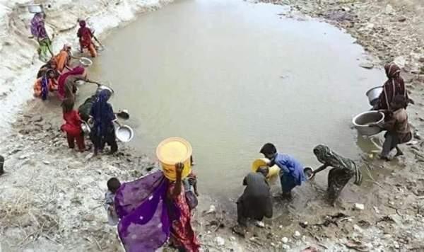 Women and children arranging dirty water from pond near Chhinni village of Kachho belt