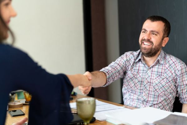 Man signing contracts and handshake with a business woman