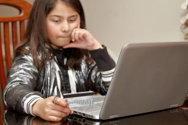 A young girl shopping online on laptop through credit card