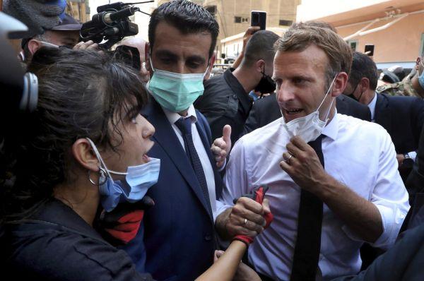 French President Emmanuel Macron (R), speaks with a female journalist