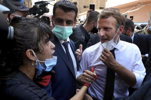 French President Emmanuel Macron (R), speaks with a female journalist