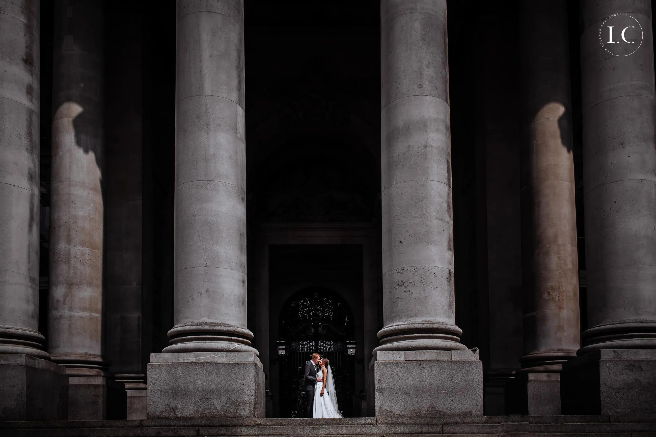 Bride and groom between two pillars