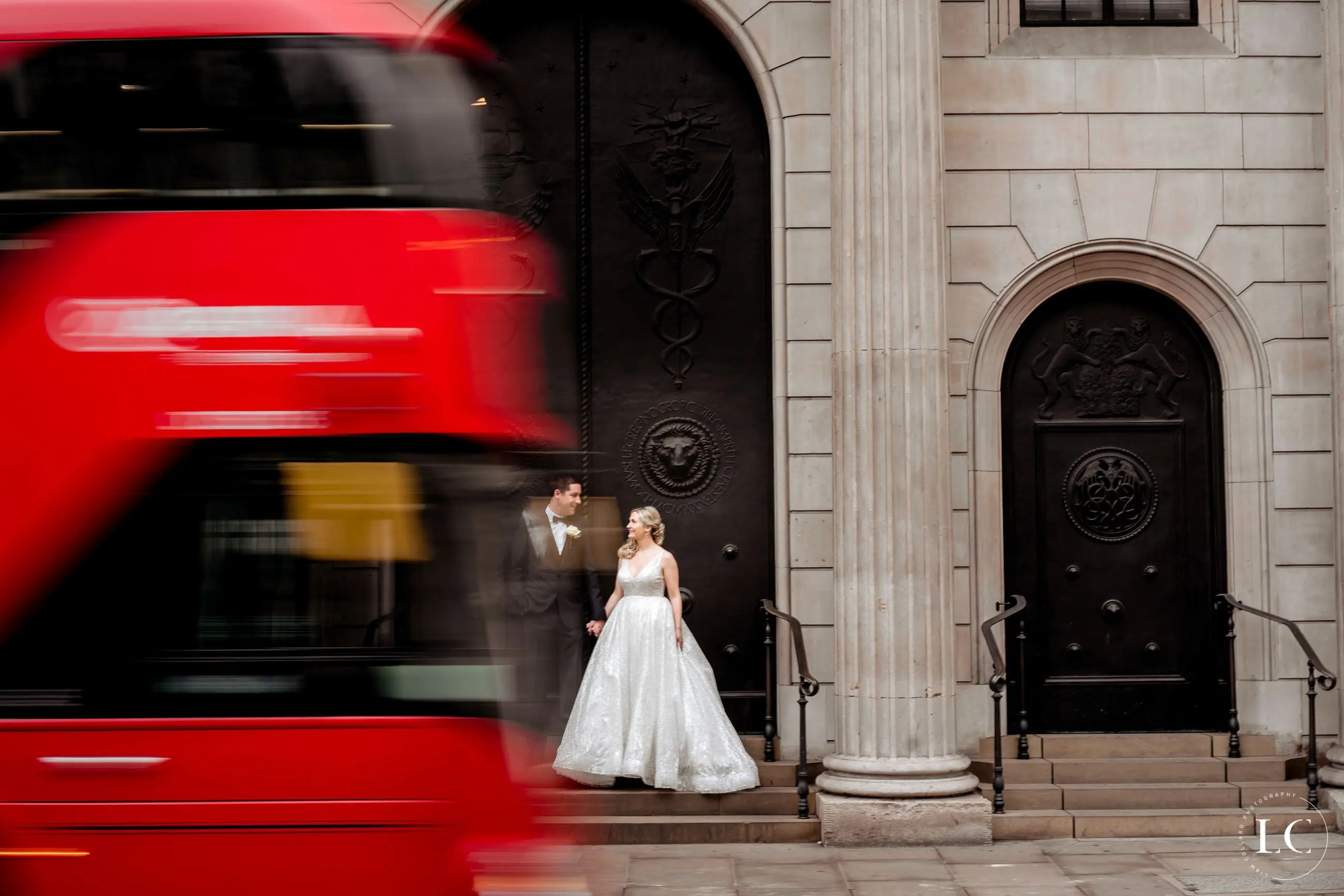 Bride and groom outside London bus