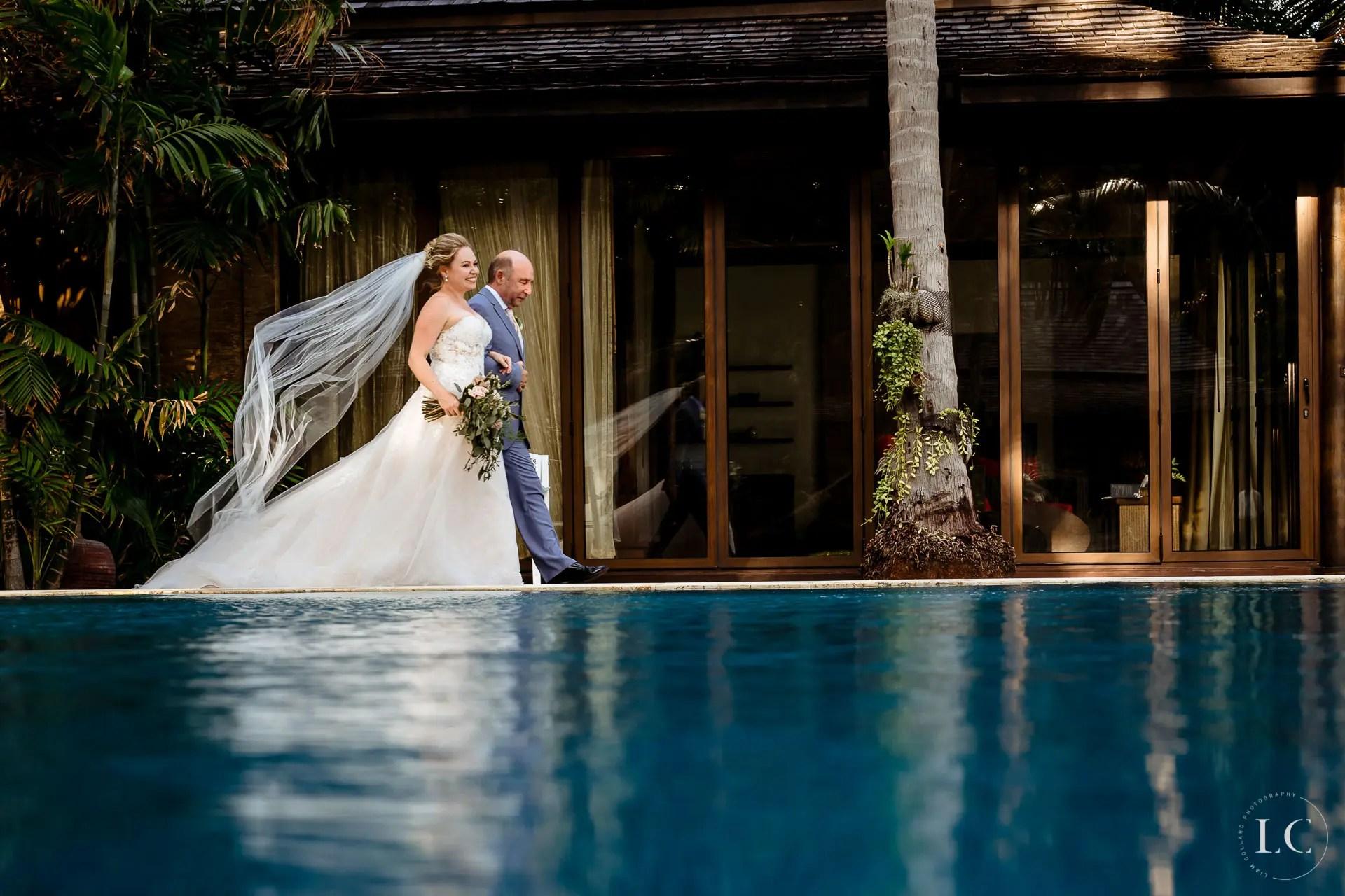 Bride and groom walking beside pool