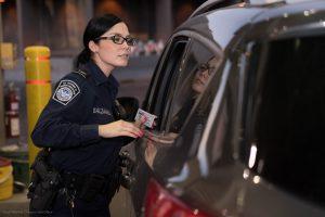Amerikansk grensevakt sjekker pasasjerer og pass i en bil.
