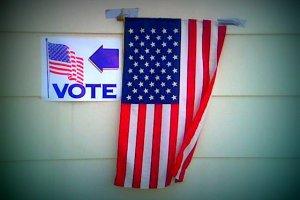 Et amerikansk flagg teipet opp med gaffa og et skilt som peker veien til stemmelokalet. Foto: Derek E. Baird CC.BY.SA.