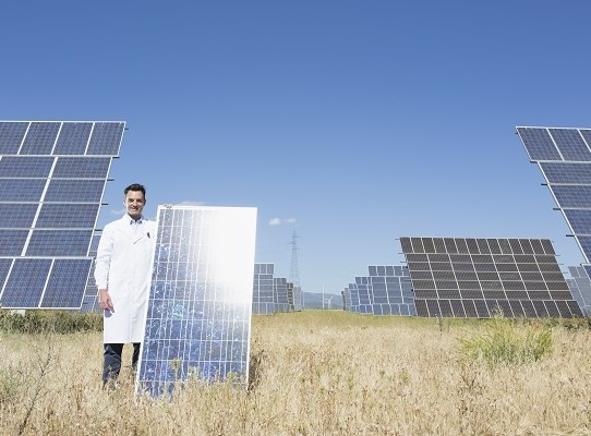 Portrait confident scientist with solar panel in sunny field