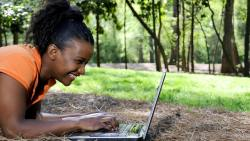 woman smiling at computer screen