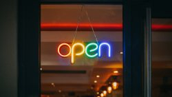 "Neon sign reading ""open"" hanging in window"