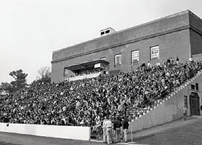 Rear of Field House with bleachers full of people.