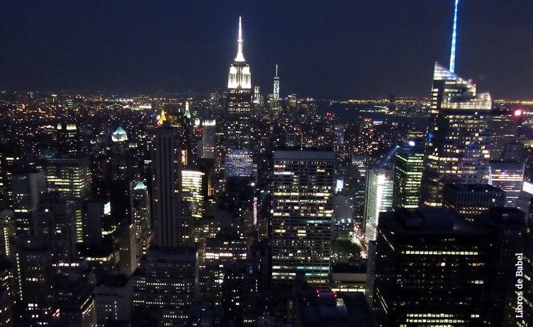 Vista nocturna de las azoteas de Nueva York tomada desde un rascacielos y con el Empire State Building al fondo