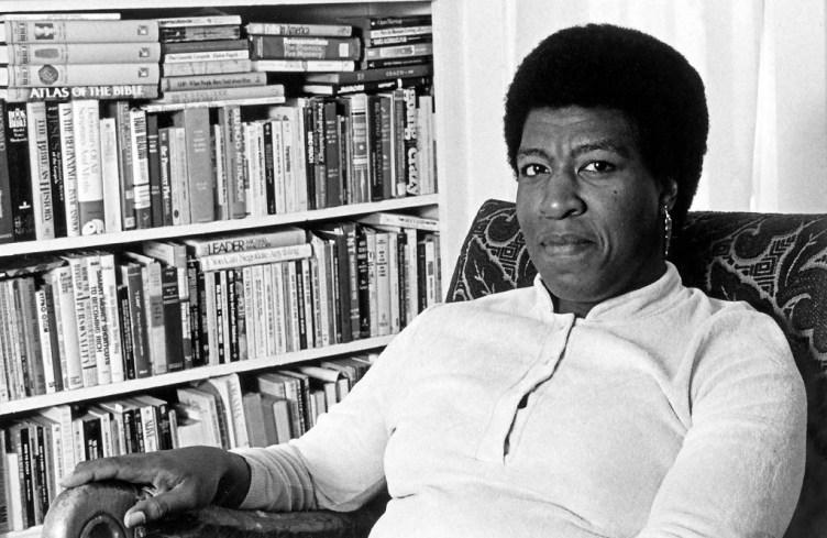 Una imagen en blanco y negro de Octavia E. Butler sentada ante su biblioteca