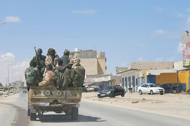 Sudanese mercenaries ride on a pickup truck in the city of Sirte